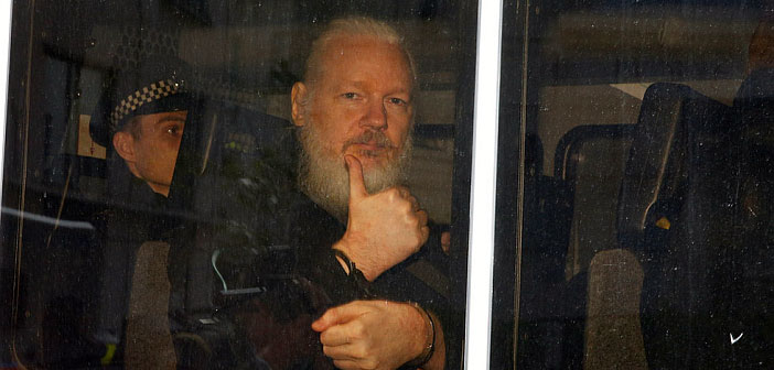 Julian Assange in handcuffs thumbs up